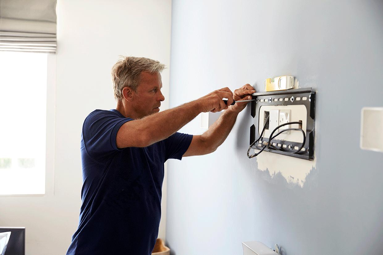 Mężczyzna wieszający telewizor na ścianie