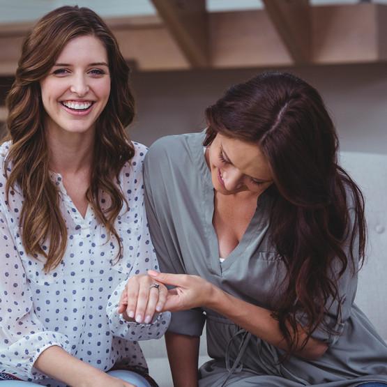 Ilustracja kobiety uwielbiane przez mężczyzn, jedna kobieta drugiej ogląda pierścionek zaręczynowy